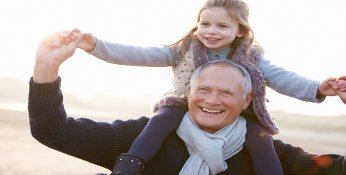 Grandfather walks on beach with Granddaughter on shoulders.